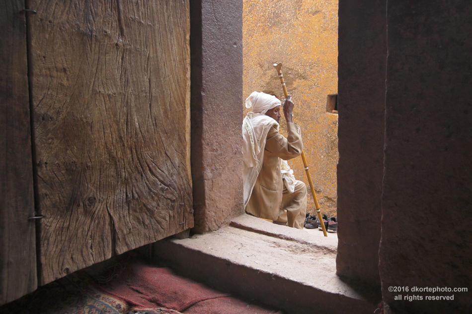 Waiting at church door. An elderly worshipper rests at a church entrance in Lalibela.