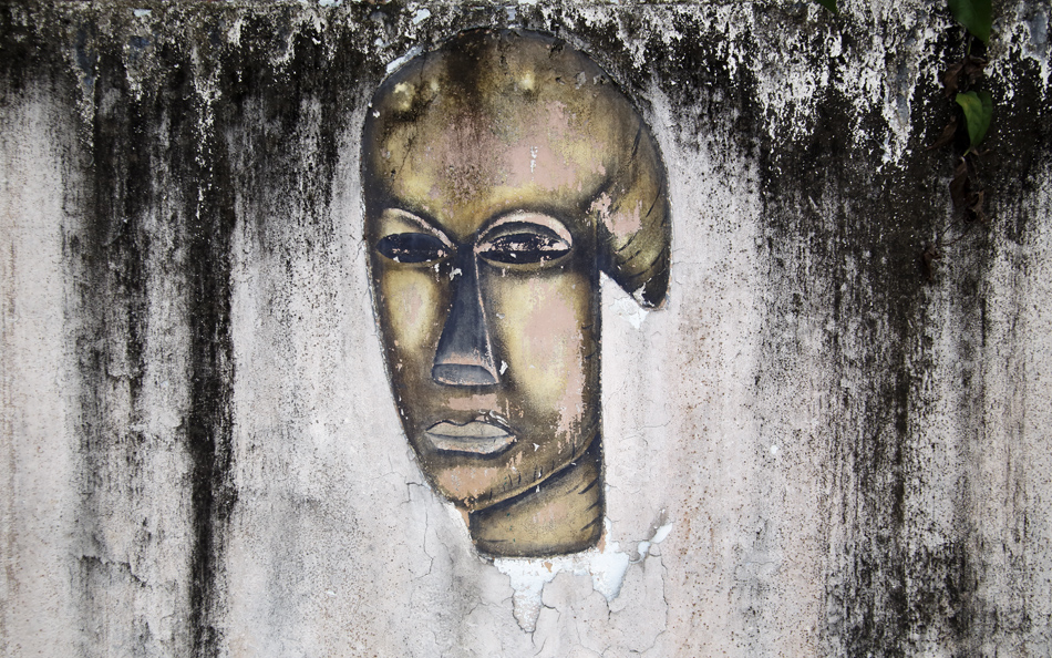 Painting of a Gabonese mask slowly reclaimed by nature at Modi-Boti Hotel in Tchibanga.