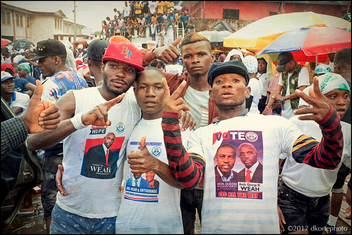 """""""So tell me sir, will America be choosing our next President?"""" Rain fails to deter the enthusiasm of Weah supporters at a rally leading up to the October elections. """"Perhaps America needs to get its own elections in order before complicating other nations."""""""
