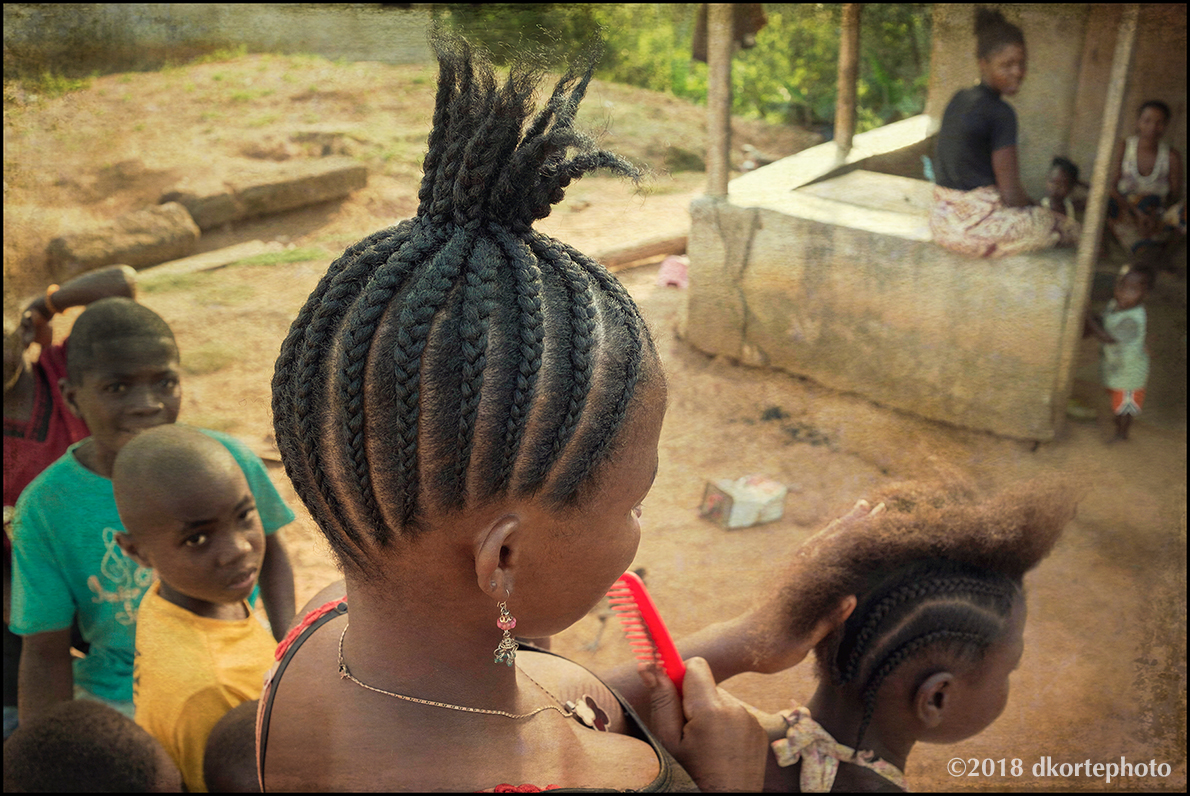 Braiding hair on a Sunday afternoon in the town square of Camp Alpha Town.