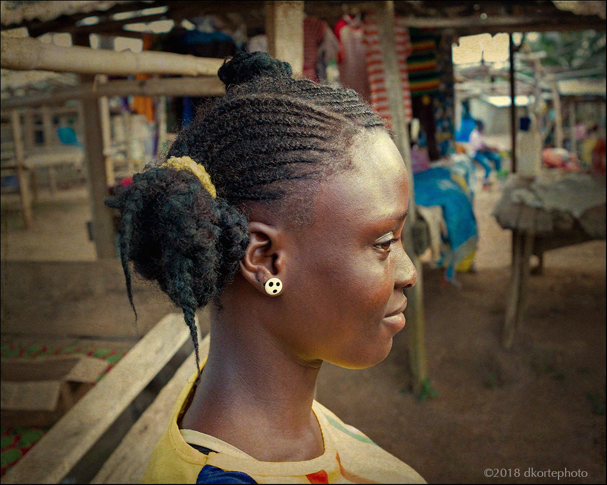 A young woman in Foya market with a variation on the cornrow style. Foya lies near the border with Sierra Leone and Guinea, in Lofa County.