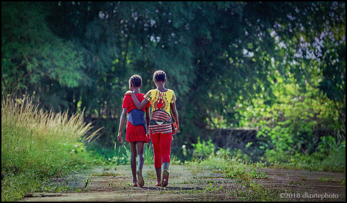 Sistahz. Walking on a seldom-used road on the edge of Bentol, aka Bensonville, Liberia.