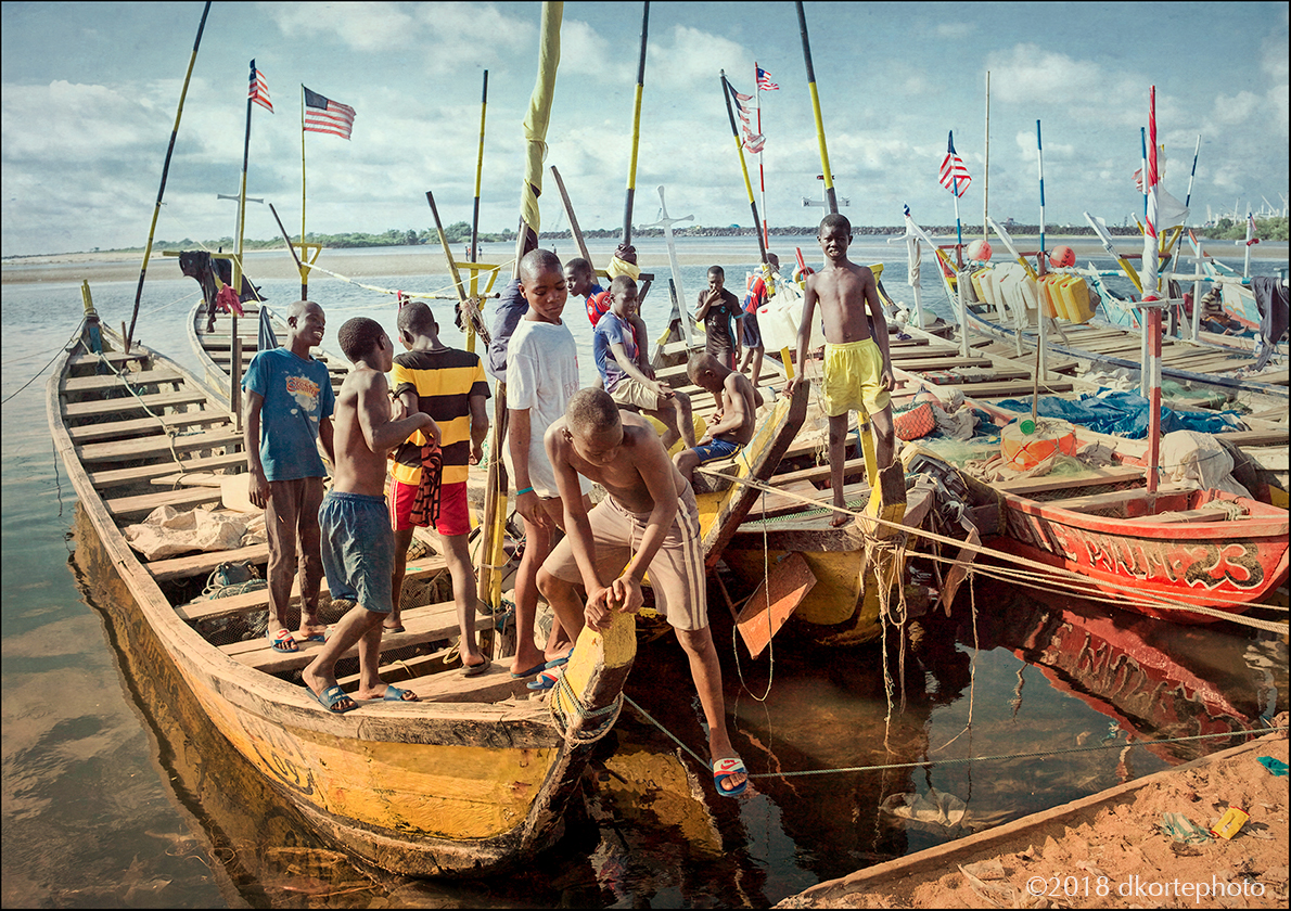Meeting at the canoes. Neighborhood boys scramble among canoes on Fante Beach.