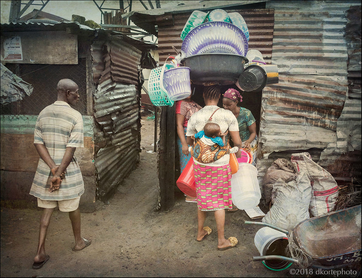 Carrying plastics and her child, a woman sells on the streets of West Point.