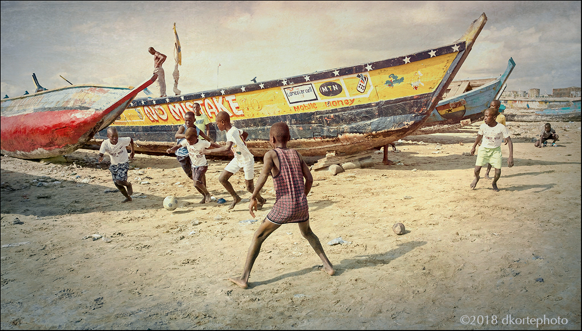 Football scramble among the canoes in dry dock, Fante Beach in the Fante fishing community of West Point.
